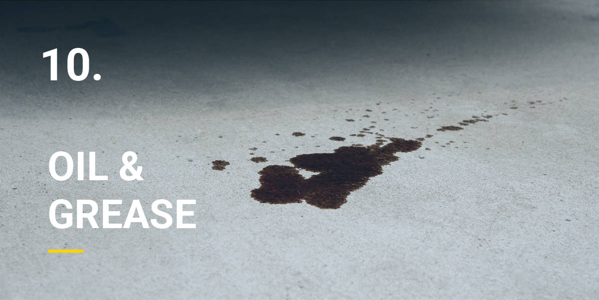 Oil and grease stains on the floor of a garage which will be treated with power washing.