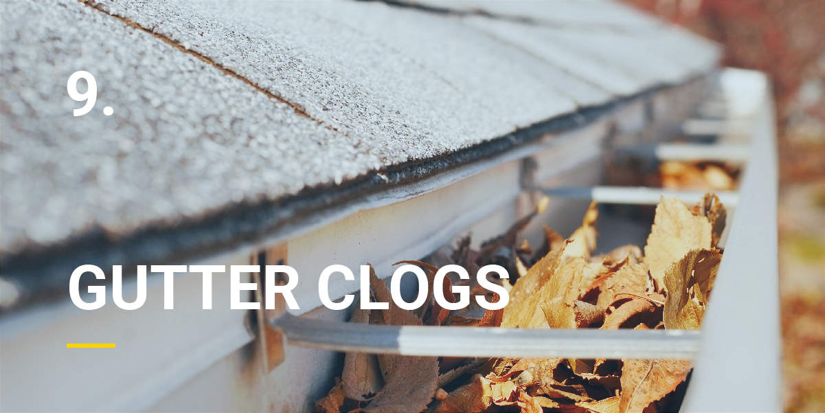 The gutter of a house is clogged with leaves.